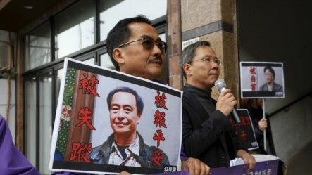 1月19日,在香港的中联办外,香港倡导民主的公民党抗议者们手持失踪书商李波和桂民海的照片。
