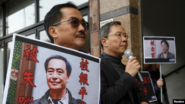FILE - Pro-democracy Civic Party protesters carry portraits of missing booksellers Lee Bo, left, and Gui Minhai outside the Chinese Liaison Office in Hong Kong, Jan. 19, 2016.