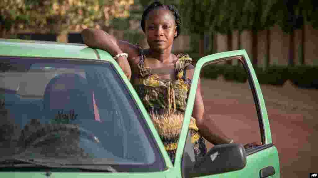 Bibata Gansgne, conductrice de taxi dans la capitale burkinabè pose à côté de son taxi dans les rues de Ouagadougou, le 1er mai 2018.