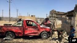 Warga sipil memeriksa lokasi ledakan bom di sebuah pasar di daerah Nahrawan, Irak (30/4).