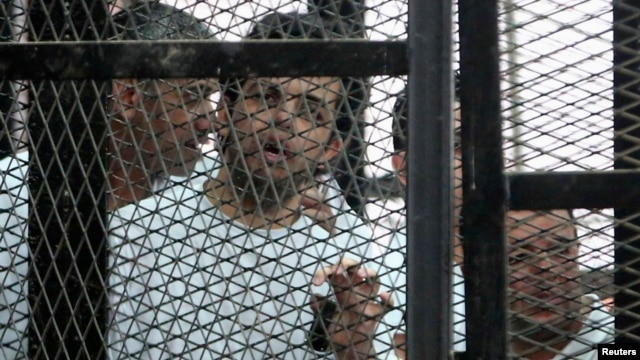 Al Jazeera's hunger-striking journalist Abdullah Elshamy stands behind bars with other prisoners at a court in Cairo, May 15, 2014.