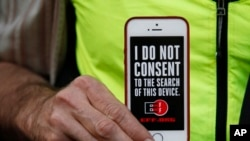 A man holds up his iPhone during a rally in support of data privacy outside the Apple store, Feb. 23, 2016, in San Francisco.