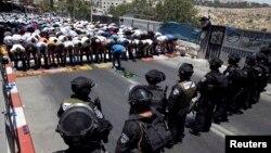 Warga Palestina melakukan shalat Jumat, sementara polisi Israel melakukan penjagaan di pinggiran Yerusalem (4/7).