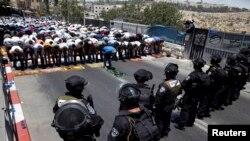 Warga Palestina melakukan ibadah sembahyang Jumat pertama dalam bulan Ramadan sementara polisi Israel berjaga di wilayah Wadi al-Joz, Yerusalem Timur (4/7).