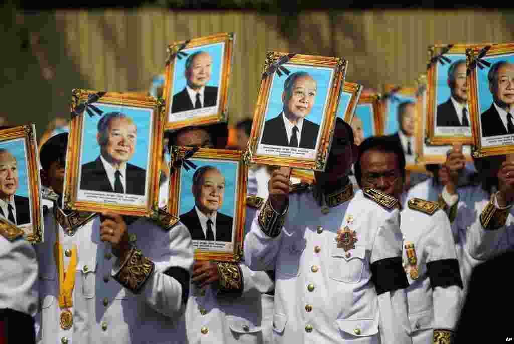参加西哈努克国王葬礼的人用西哈努克像遮挡烈日。