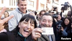"Juan Lopez holds his lottery ticket with the winning number of Spain's Christmas Lottery ""El Gordo"", together with his daughter Pilar in La Eliana near Valencia, Dec. 22, 2014."