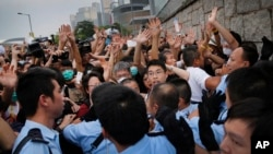 Student protesters resist during change of shift for local police but backed down after being reassured they could reoccupy the pavement outside the government compound's gate in Hong Kong, Oct. 2, 2014.