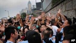 在香港政府总部大门外,抗议学生在警察换班之际与警察发生推搡,在被告知他们可以重新占据人行道后,学生退让。(2014年10月2日)