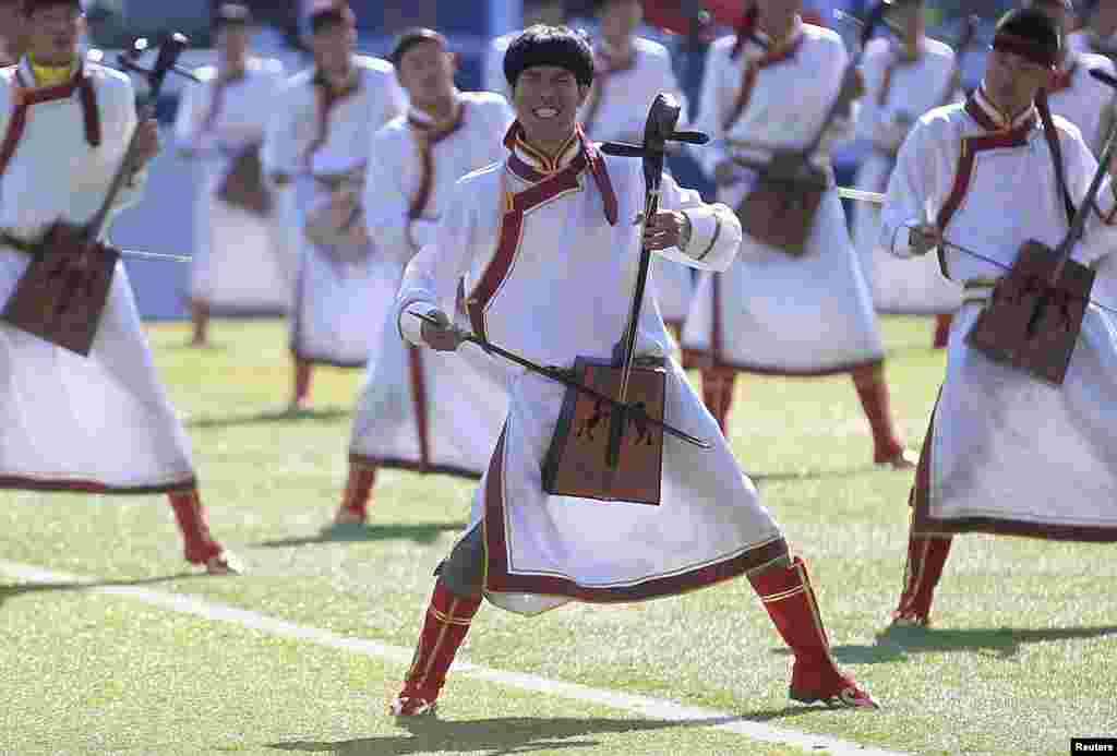 Participants play traditional Mongolian instruments during a performance at the opening ceremony of Nadam Fair in Xilinhot, Inner Mongolia Autonomous Region.