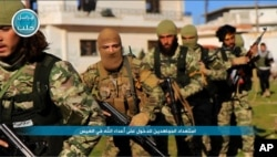 FILE - This photo posted on the Twitter page of Syria's al-Qaida-linked Nusra Front on April 1, 2016, shows fighters from al-Qaida's branch in Syria, the Nusra Front, marching toward the northern village of al-Ais in Aleppo province, Syria.