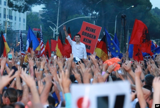 Lulzim Basha, leader of the main opposition Democratic Party, standing in background, flashes the victory sign during an anti-government protest in Tirana, Albania, June 8, 2019.