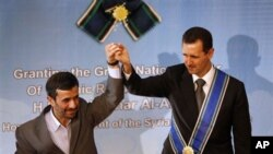 In this file photo, Iranian President Mahmoud Ahmadinejad, left, holds up the hand of his Syrian counterpart Bashar Assad after he awarded Iran's highest national medal.