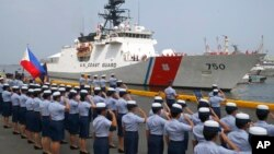 Philippine Coast Guard personnel salute to welcome the U.S. Coast Guard National Security Cutter Bertholf (WMSL 750) as it arrives for a port call in the first visit by a U.S. cutter in over seven years, Wednesday, May 15, 2019 in Manila, Philippines. (AP