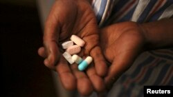 FILE - Nine-year-old Tumelo shows off antiretroviral (ARV) pills before taking his medication at Nkosi's Haven, south of Johannesburg, Nov. 28, 2014.