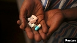 Nine-year-old Tumelo shows off antiretroviral (ARV) pills before taking his medication at Nkosi's Haven, south of Johannesburg, Nov. 28, 2014.