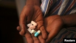Nine-year-old Tumelo shows off antiretroviral (ARV) pills before taking his medication at Nkosi's Haven, south of Johannesburg, in 2014.