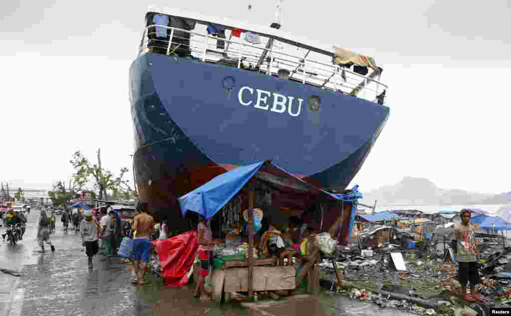 Typhoon survivors sell goods in a makeshift store next to a ship that was swept ashore by Super Typhoon Haiyan last month, in Tacloban city in central Philippines.