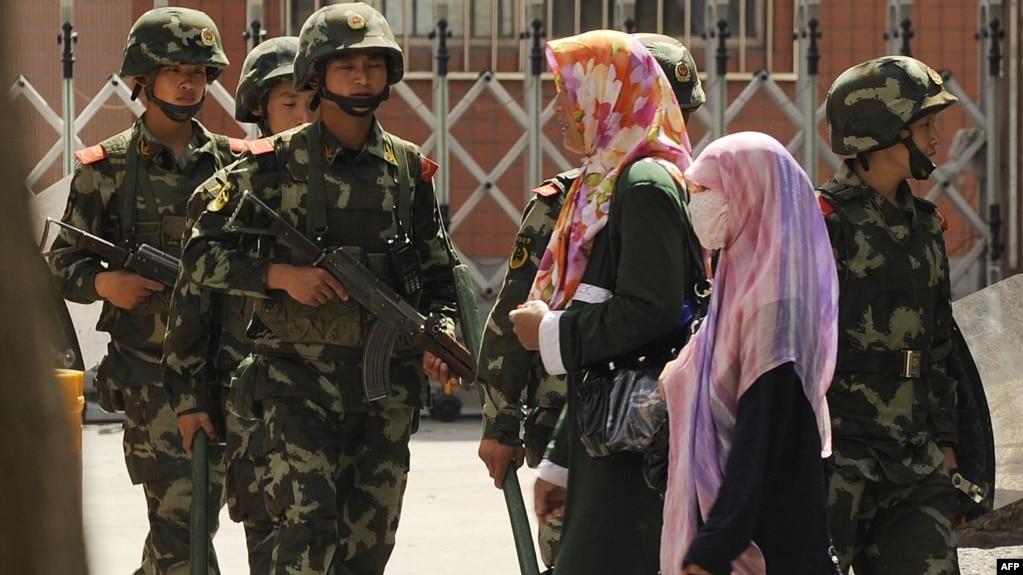 Phụ nữ Hồi giáo Duy Ngô Nhĩ đi trên đường phố ở Urumqi, nơi lực lượng bán quân sự Trung Quốc đang tuần tra.