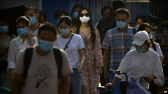 People wearing face masks to protect against the coronavirus wait to cross an intersection in the central business district in Beijing, Wednesday, July 15, 2020. China is further easing restrictions on domestic tourism after reporting no new local cases o