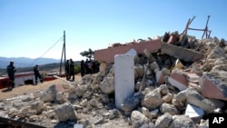Firefighters stand next to a demolished Greek Orthodox church of Profitis Ilias after a strong earthquake in Arkalochori village on the southern island of Crete, Greece, Sept. 27, 2021.