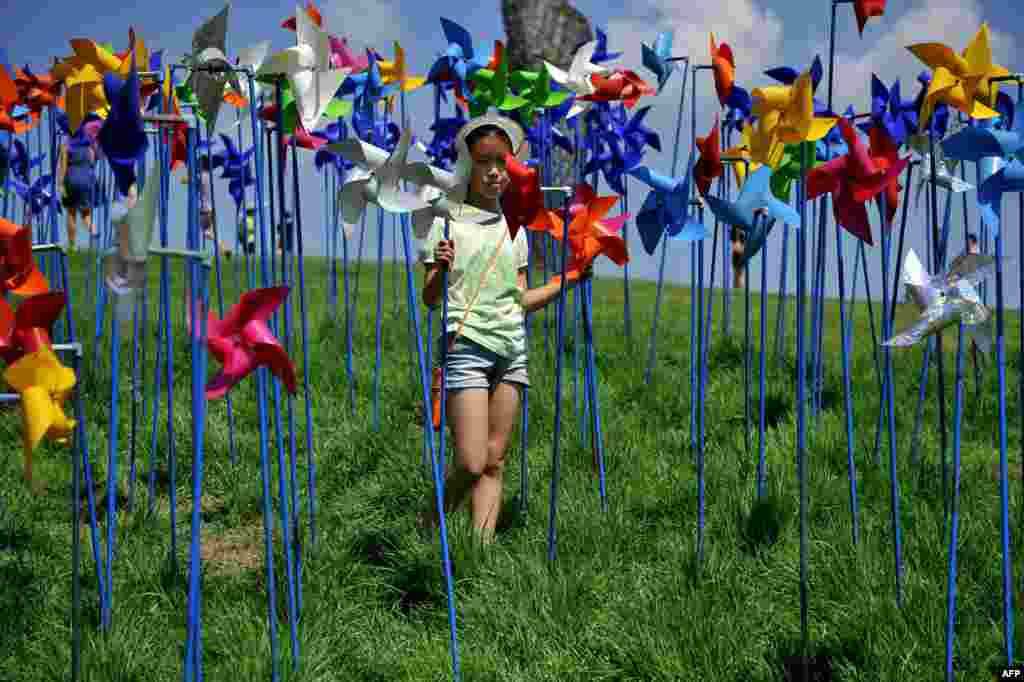 A girl spins pinwheels at a peace park, which was built to deliver the peace between North and South Korea, near the border village of Panmunjom in Paju, north of Seoul, South Korea.