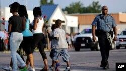 Polisi siaga di kota Ferguson (18/8). Penembakan terakhir di kota St. Louis, Missouri menambah kompleks permasalah di negara bagian Missouri.