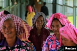 FILE - Women arrive at the entrance gate to the Extraordinary Chambers in the Courts of Cambodia (ECCC) for the trial hearing on evidences of forced marriage and rape during the Khmer Rouge regime, on the outskirts of Phnom Penh, Cambodia, Aug. 23, 2016.
