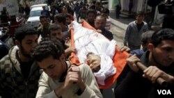 Warga Palestina mengangkut korban tewas akibat serangan udara Israel untuk dimakamkan di Gaza.