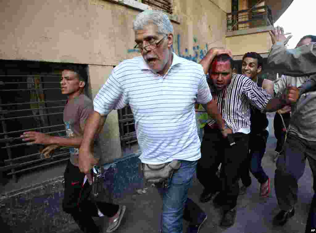 An Egyptian man with a pistol and opponents of Egypt's ousted President Mohamed Morsi detain a suspected Morsi supporter who was wounded during clashes in Cairo, July 22, 2013.