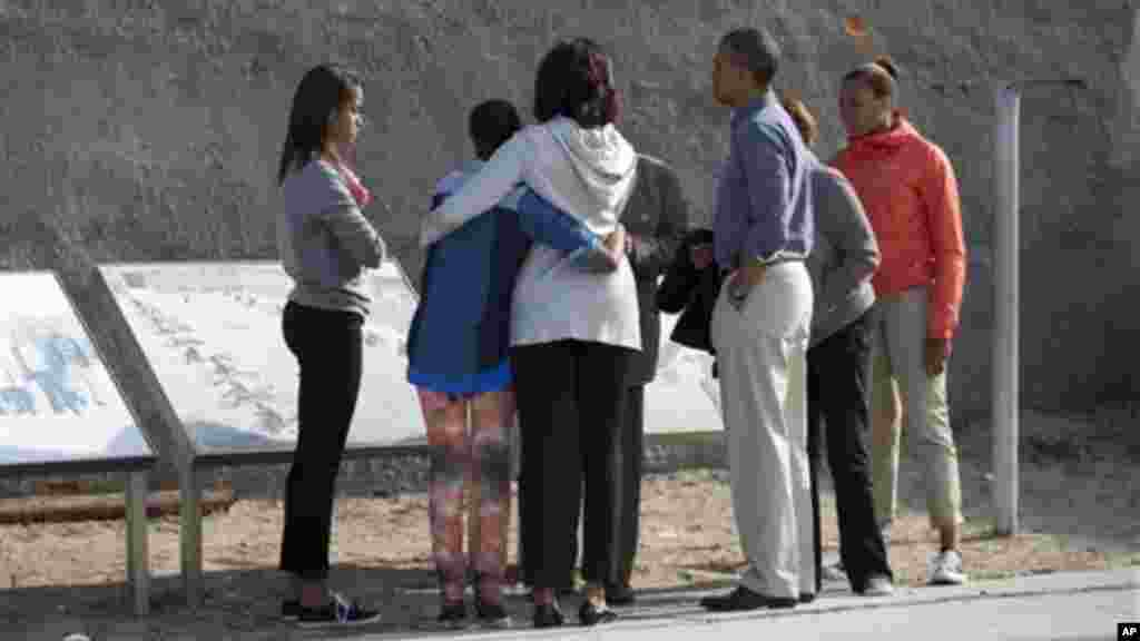 Malia Obama, Sasha Obama, first lady Michelle Obama, and Ahmed Kathrada a former prisoner with Mandela, stand in the courtyard of the prison on Robben Island.