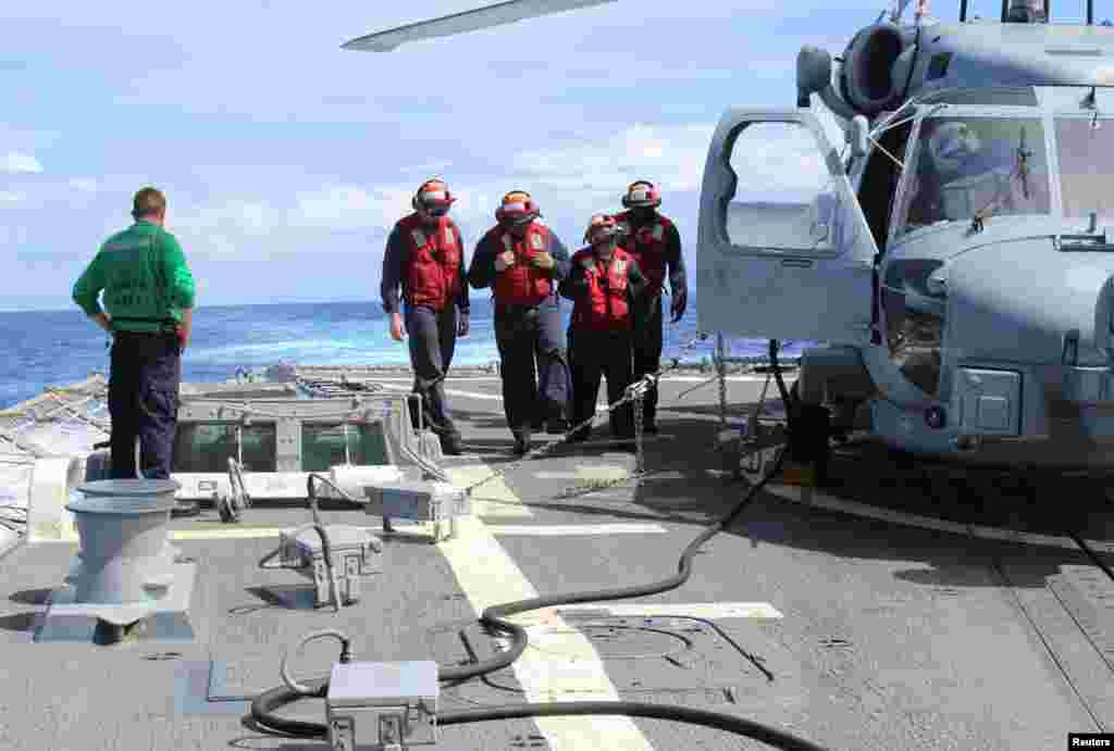 Sailors inspect the flight deck of the USS Kidd in this U.S. Navy handout picture, March 16, 2014.