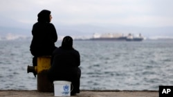 FILE - Two women sit on a dock of a refugee camp which houses about 3,200 refugees and migrants, in the western Athens suburb of Skaramagas, Aug. 25, 2016.