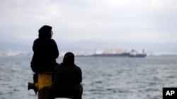 Deux femmes sont assises sur un quai d'un camp de réfugiés qui abrite environ 3.200 réfugiés et migrants, dans la banlieue ouest de Skaramagas, à Athènes, le 25 août 2016.