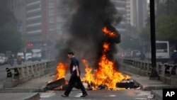 Seorang pejalan kaki berjalan melewati barikade yang sengaja dibakar demonstran anti-pemerintah untuk memblokir jalan besar di Chacao, Caracas, Venezuela, (24/2).