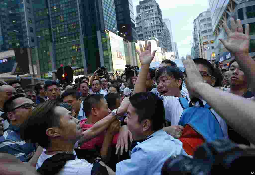 A local policeman scuffles with residents and pro-Beijing supporters as they try to attack a student pro-democracy activist in Mong Kok district, Oct. 3, 2014.
