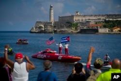 """ພວກນັກທ່ອງທ່ຽວ ຢືນຢູ່ເທິງເຮືອໄວຂອງພວກເຂົາ, ໂດຍມີທິວທັດຢູ່ດ້ານຫຼັງ ຂອງຜາສາດ """"El Morro"""", ໃນນະຄອນຫຼວງ Havana ຂອງ Cuba, ວັນທີ 17 ສິງຫາ 2017."""