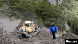 French Gendarme Bruno Hermignies stands by a bulldozer clearing a path to the crash site of the Germanwings Airbus A320 in the mountains, near Seyne-les-Alpes, French Alps, March 30, 2015.