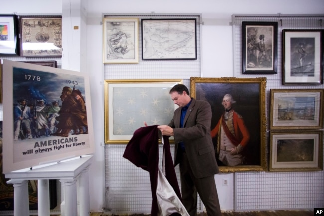 In this June 5, 2014 photo, Scott Stephenson, Director of Collections and Interpretation, uncovers the recently conserved George Washington's flag.