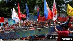 Demonstrators display a part of a fishing boat with anti-China protest signs during a rally by different activist groups over the South China Sea disputes, outside the Chinese Consulate in Makati City, Metro Manila, Philippines, July 12, 2016.