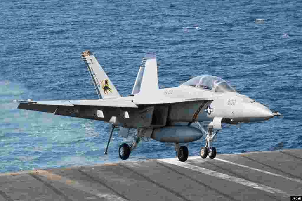 An F/A-18F Super Hornet attached to the Fighting Black Lions of Strike Fighter Squadron (VFA) 213 lands aboard the aircraft carrier USS George H.W. Bush (CVN 77) after conducting strike missions against ISIL targets. George H.W. Bush is supporting maritime security operations and theater security cooperation efforts in the U.S. 5th Fleet area of responsibility, Arabian Gulf, Sept. 23, 2014. (U.S. Navy photo by Mass Communication Specialist 3rd Class Brian Stephens/Released)