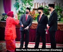 Tri Rismaharini, Wali Kota Surabaya, yang baru dilantik menjadi Menteri Sosial berbincang dengan beberapa menteri lainnya, di Istana Negara, Rabu, 23 Desember 2020. (Foto: Biro Pers Sekretariat Presiden)