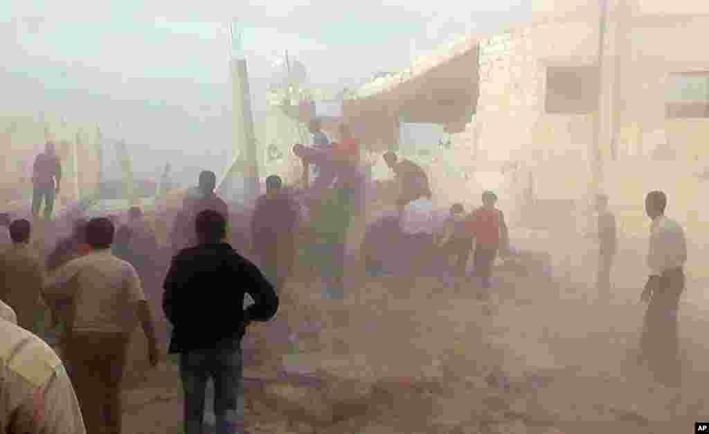 정부군의 공격으로 부서진 건물 잔해 속에서 생존자 구조작업을 벌이고 있는 시민들