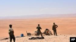 Foto ki montre militè siryen ak gwoup pwo lame Siri a ki nan zòn Deir el-Zour kote batay tap dewoule pou reprann kontwòl vil sa nan men militan Eta Islamik yo.
