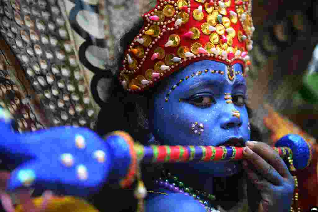 A Bangladeshi youth dressed as the Hindu god Lord Krishna takes part in a procession during celebrations for the Janmashtami festival in Dhaka.