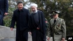 ປະທານປະເທດຈີນ ທ່ານ Xi Jinping, ຊ້າຍ, ຕ້ອນຮັບທ່ານ Hassan Rouhani ປະທານາທິບໍດີ ໃນຂະນະທີ່ທ່ານທຳການຢ້ຽມຢາມຢ່າງເປັນທາງການທີ່ພະລາຊວັງ Saadabad,ເຕຫຣານ ອິຣານ, 23 ມັລກອນ, 2016.