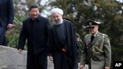 Presiden China Xi Jinping (kiri) disambut Presiden Iran Hassan Rouhani setibanya di Istana Saadabad di Teheran, Iran (23/1).