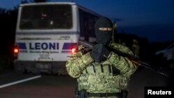 21일 우크라이나 동부 도네츠크에서 포로교환이 이루어진 가운데, 한 정부군 병사가 주변을 지키고 있다.