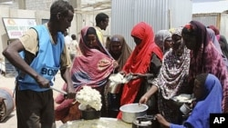 Women and children from southern Somalia line up to receive cooked food distributed by World Food Program (WFP) in Mogadishu, Somalia, August 20, 2011.
