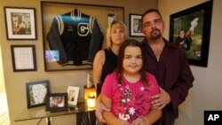 Gary and Johanna Cuccia with their daughter Alisa at their home in Pennsylvania in 2010. Behind them are photos of another daughter, Demi, who was stabbed to death by her boyfriend on her 16th birthday after breaking up with him.