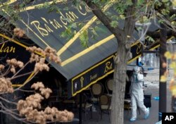 An investigator works outside the Bataclan concert hall in Paris, Nov. 14, 2015.